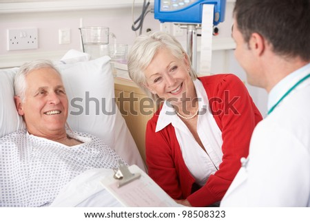 Doctor talking to senior couple on USA Hospital ward