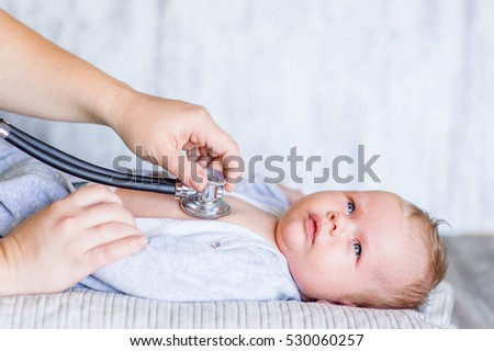 Doctor using a stethoscope to listen to kid's chest checking heartbeat