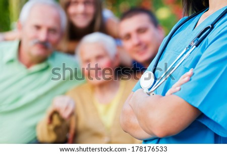 Doctor with stethoscope and happy family in the background medical care concept.