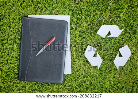 Documents in a black leather folder lie over green grass next to a white cutout paper recycling symbol, top view.