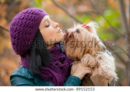 dog in girls hand lick her chin