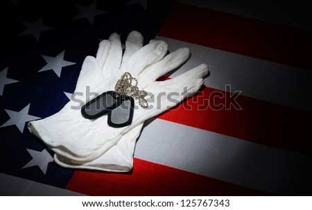 Dog tag and white gloves on U.S. flag