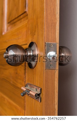 door knob and keyhole on wooden door, close up image