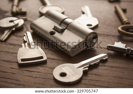 door lock with keys on wooden surface