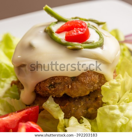 Double beef burger with melted cheese, asparagus and fresh vegetables