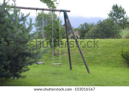 double child's wood swing in the garden.