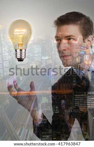 Double exposure of Business man holding light bulb with cityscape