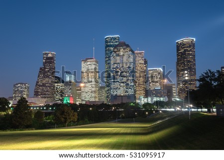 Downtown Houston illuminated at blue hour with green park lawn and modern skylines light. It is the most populous city in Texas and the fourth-most in United States. Architecture and travel background