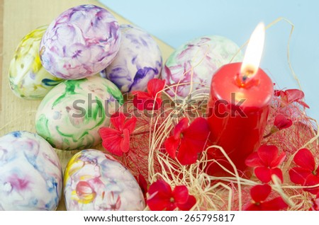 Dozen of hand colored Easter eggs and a red burning candle decorated with red flowers and ribbons