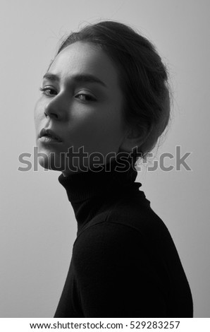 Dramatic black and white portrait of young beautiful girl with freckles in a black turtleneck on white background in studio