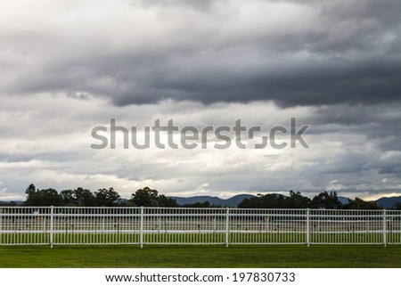 Dramatic blue and grey fractus storm clouds at sunset over an empty Australian horse race course with trees and mountains in the distance