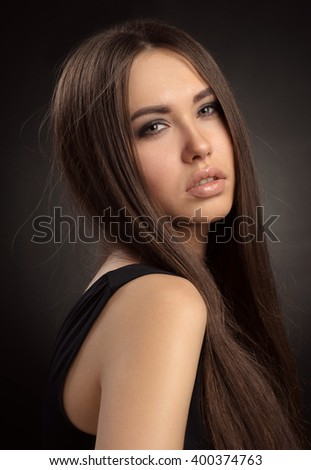 Dramatic portrait of a young beautiful girl on a dark background in the studio