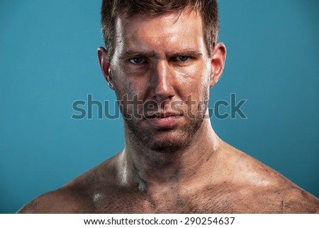 Dramatic portrait of young dirty man isolated on blue background