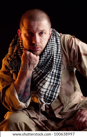 Dramatically lit army officer in camo clothes and arabian scarf