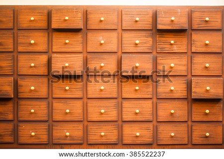 Drawers with blank tags in vintage furniture module.