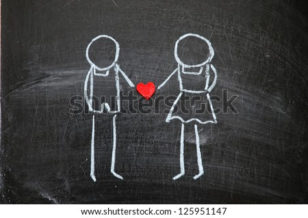 Drawing on a blackboard by hand, the man and the woman hold heart in a hand