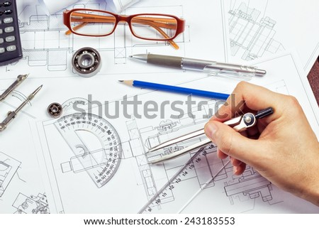 Drawings, pencil, pen, protractor, compass bearings, calculator on the table. Man's hand with a compass. The process of drawing. Department of engineering design.