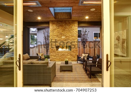 Dreamy Outdoor Covered Patio With Stone Fireplace, A Beadboard Ceiling With  Skylight, Rattan Armchairs