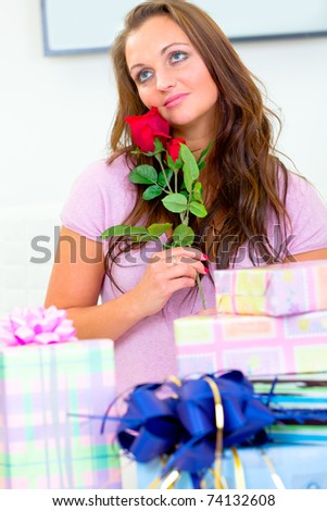 Dreamy pretty woman sitting among gifts and holding rose in hands