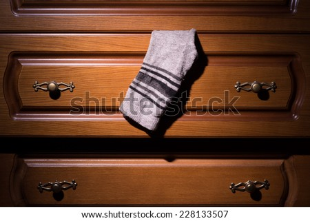 dresser from which protrudes a sock