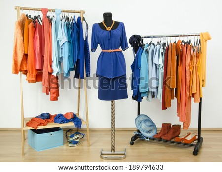 Dressing closet with complementary colors blue and orange clothes arranged on hangers and an outfit on a mannequin. Wardrobe full of all shades of blue an orange clothes, shoes and accessories.