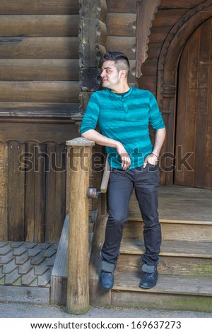 Dressing in a green striped long sleeves Henley shirt, black pants and leather boots, a young handsome guy is standing outside a wooden house and taking a break. / Waiting for You