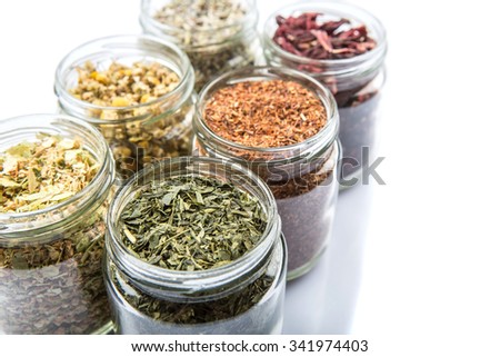 Dried herbal tea variety lavender, hibiscus, chamomile, linden flower, rooibos, Japanese green tea in mason jars over white background