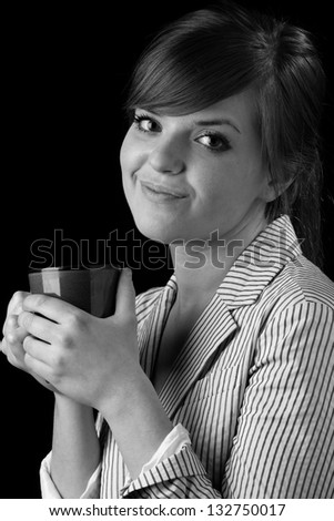 Drinking Coffee - This is a black and white image of a young business woman holding a cup of coffee. Shot on a black background.