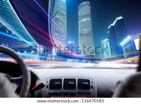 Driver's hands on a steering wheel of a car and night scene