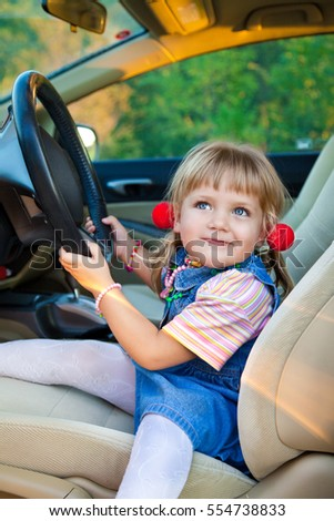 Driving little girl. Beautiful child sitting in a car