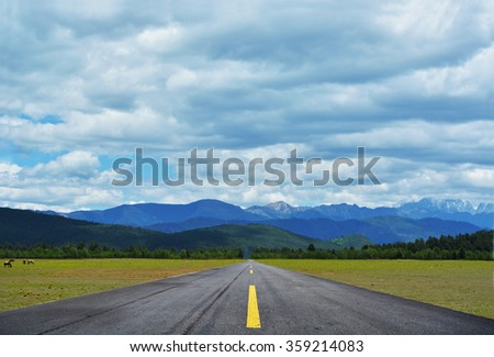 Driving on an empty asphalt road towards the mountain