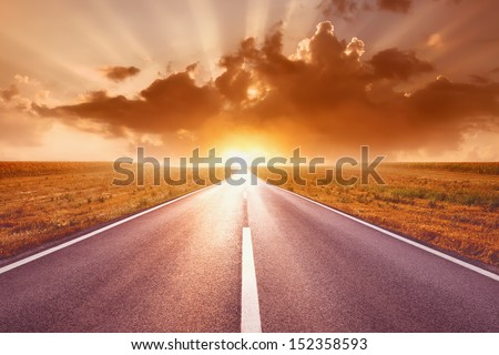 Driving on an empty highway to the sun