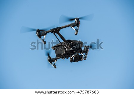 Drone-quadrocopter with camera hovers on the blue sky/Drone flying in the sky