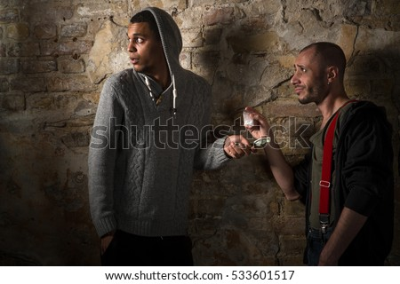 Drug addict buying narcotics and drugs in drug dealer. Drug dealer selling different types of drugs and receiving much money from it.