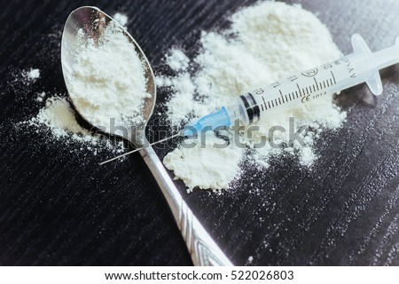 drug use, addiction and substance abuse concept - close up of spoon and syringe with crack cocaine drug dose