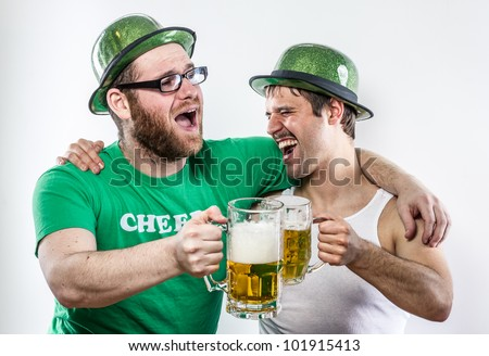 Drunk Irish friends on Saint Patrick's Day toasting large mugs of tavern beer while singing together for the holidays