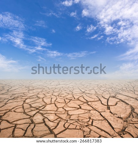 Dry cracked soil in drought land under blue sky.