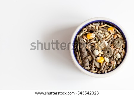 dry food for rodents in bowl white background top view