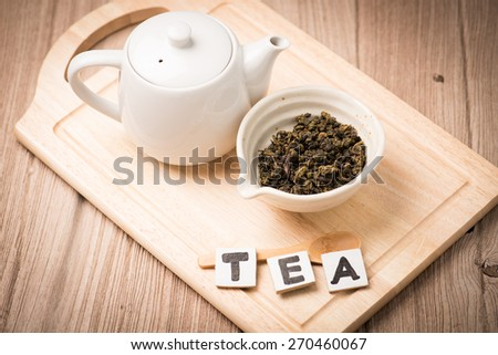 dry tea leaf in ceramic bowl wit whith pot on wood background