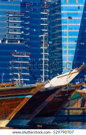 DUBAI,UAE - JAN.24: looking across Dubai Creek with office building on the left and old dhow boat which are used for shipping goods and sometimes as restaurant on 24th of january 2010 in Dubai, UAE.