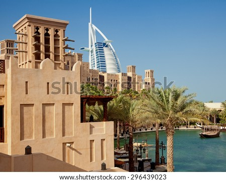 DUBAI, UAE - JANUARY 14, 2013: Traditional windcatcher and Arabic style buildings of Madinat Jumeirah in front of Burj Al Arab. Burj Al Arab is a luxury 7 star hotel, built on an artificial island.