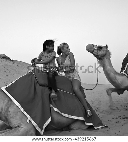 Dubai, United Arab Emirates - June 18, 2010: funny scene with a frightened girl and a camel