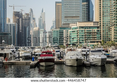 DUBAI, UNITED ARAB EMIRATES - JUNE 25, 2016: Luxury Yacht and modern skyscrapers in famous Dubai Marina. Marina - artificial canal city, carved along a 3 km stretch of Persian Gulf shoreline.