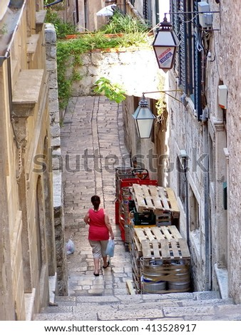 DUBROVNIK, CROATIA - CIRCA JUNE 2008: Woman walks through an alley surrounded by stone buildings