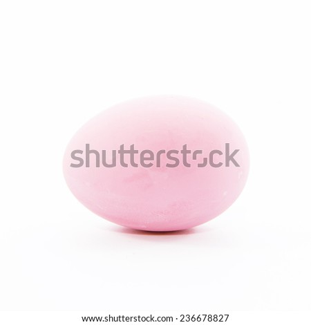 Duck's egg preserved in potash with pink eggshell on white background