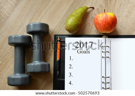 Dumbbells with fruits and open notebook on wooen desk. Healthy resolutions for the New Year 2017.