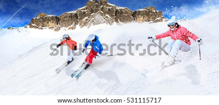 Dynamic picture of three ski driver on the piste in Alps