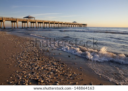 Early morning sunrise on a shell filled beach with fishing pier in the