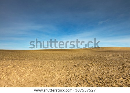 Early springtime plowed field landscape. Polish field at sunny spring day under blue sky