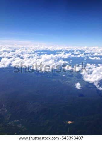 Earth landscape viewed from airplane. Earth surface under the white clouds and blue sky from aerial view. Cloudy weather covering residential land and argriculture land.